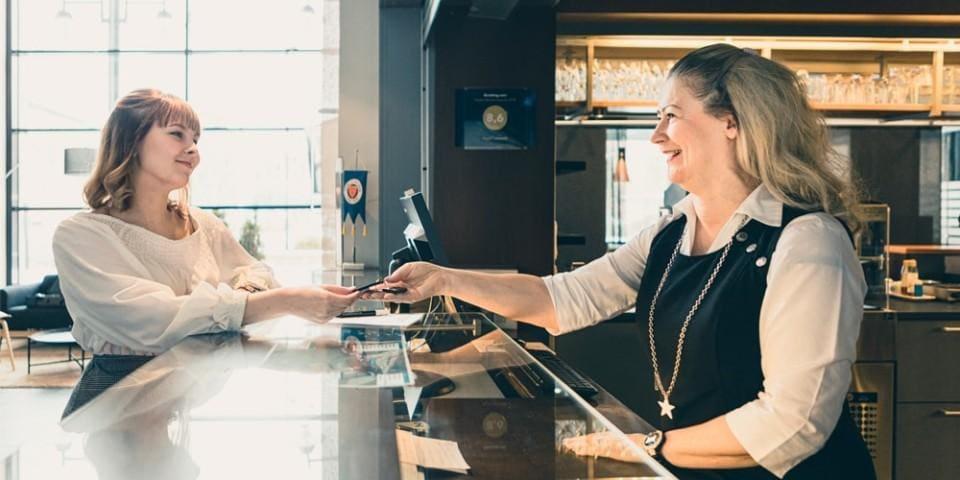 Hotellivirkailija luovuttamassa naiselle avainta hotellin vastaanotossa.
