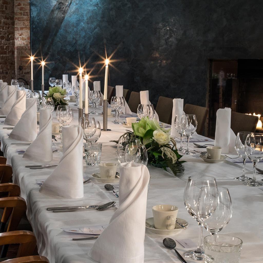 Merikoski-sali on tunnelmallisen kaunis juhlatila, jonka pöydässä juhlakattaus kynttilöineen ja kankaisine lautasliinoineen.