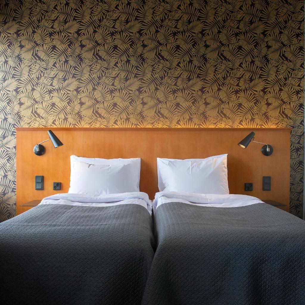 Hotelli Lasaretin viihtyisä kahden hengen huone, jonka värimaailma rauhoittaa.