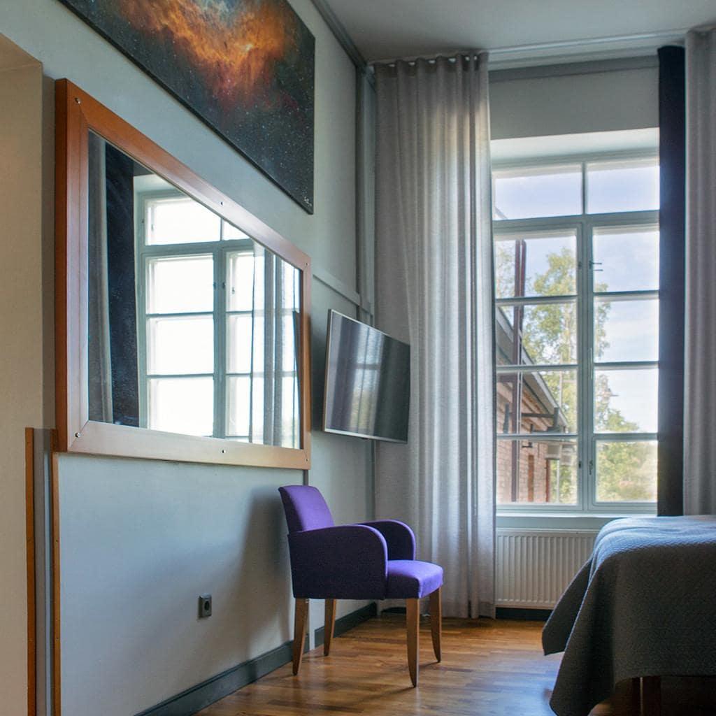 Hotelli Lasaretin sviitissä on kaksi makuuhuonetta ja oleskeluhuone, kuvassa toinen makuuhuoneista isoine peileineen ja nojatuoleineen.