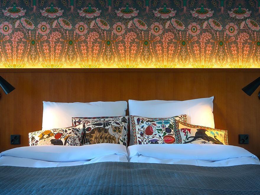 Jaakko Mattilan suunnittelema värikäs taiteilijahuone, jossa kuviollinen tapetti huoneen päätyseinällä.