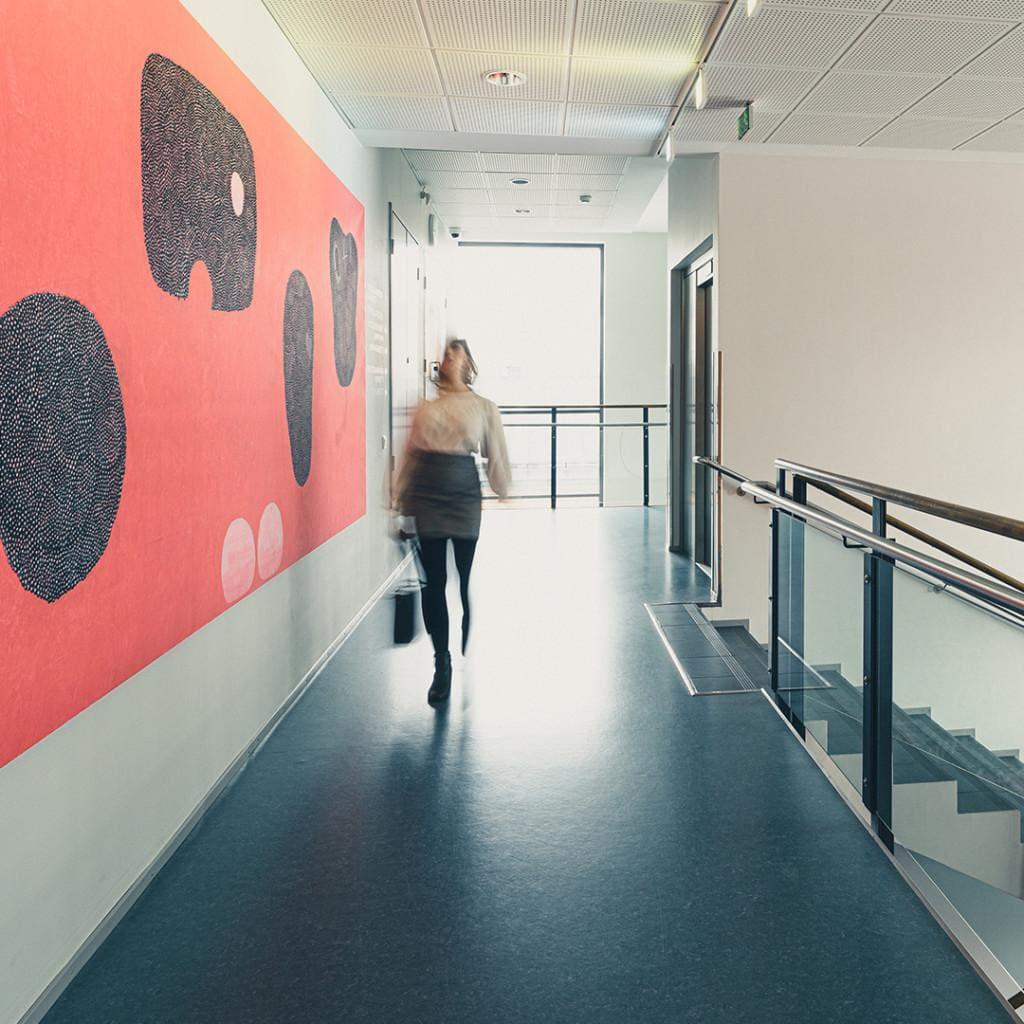 Lasaretissa kokoustat toimivissa tiloissa taiteen ympäröimänä. Nainen kävelee ison, värikkään taulun ohitse.