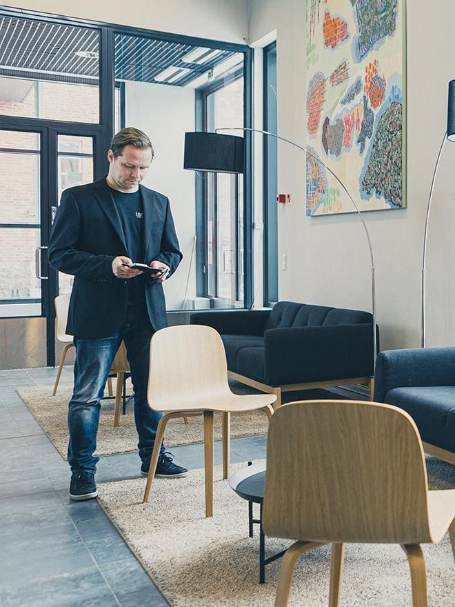 Mies katselee puhelintaan Lasaretin aulassa, jossa voi odotella kokouksen alkua.