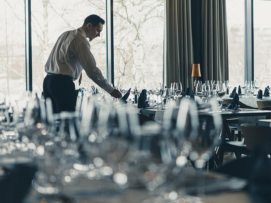 Miestarjoilija kattaa Joki-salin pöytiä.
