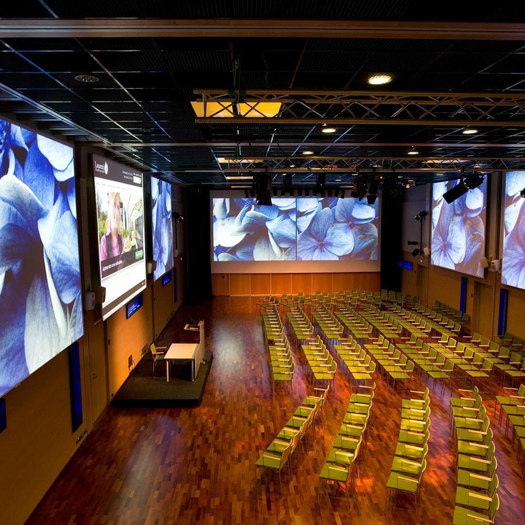 Tuolit järjestetty luentoa varten Aurora-salissa, jossa valkokankaille on heijastettu näyttävä esitys.