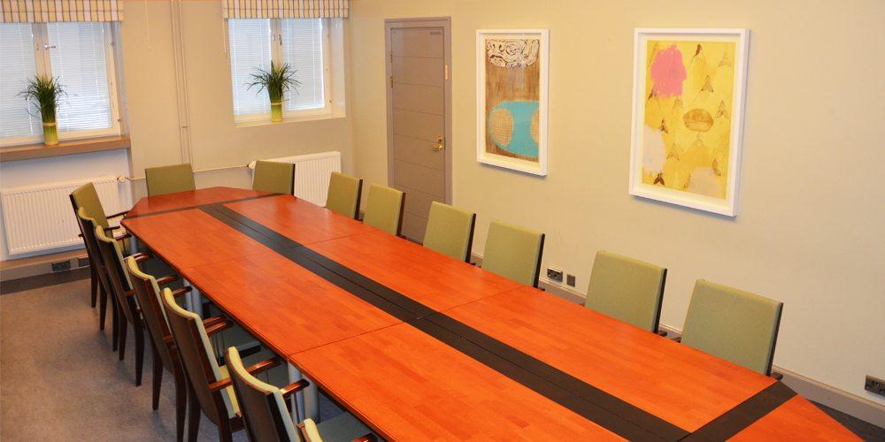 Pitkä pöytä ja taidemaalauksia Mimmi Cederqvistin kabinetissa.