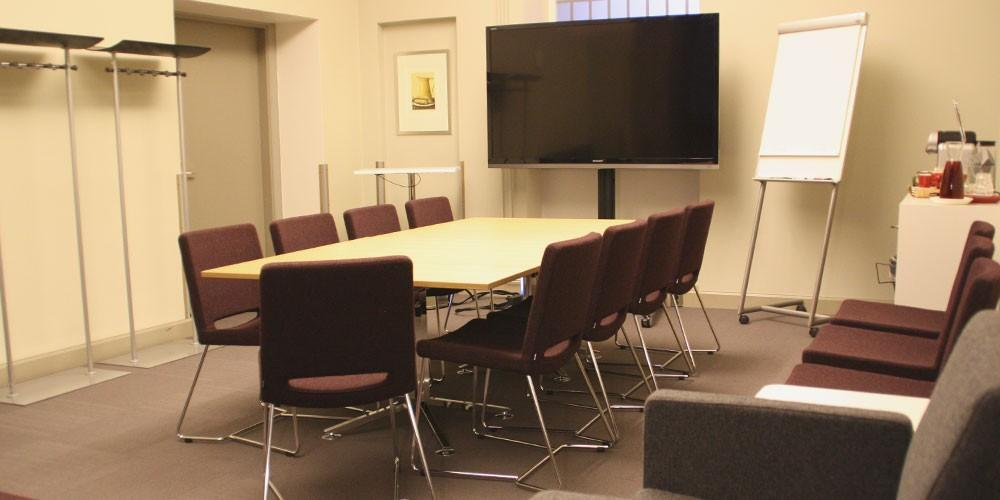 Neuvottelupöytä ja näyttönä toimiva televisio Naima Kurvisen kabinetissa.