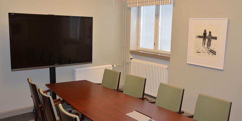 Volla-kabinetin pöytä tuoleineen sekä näyttönä toimiva televisio.