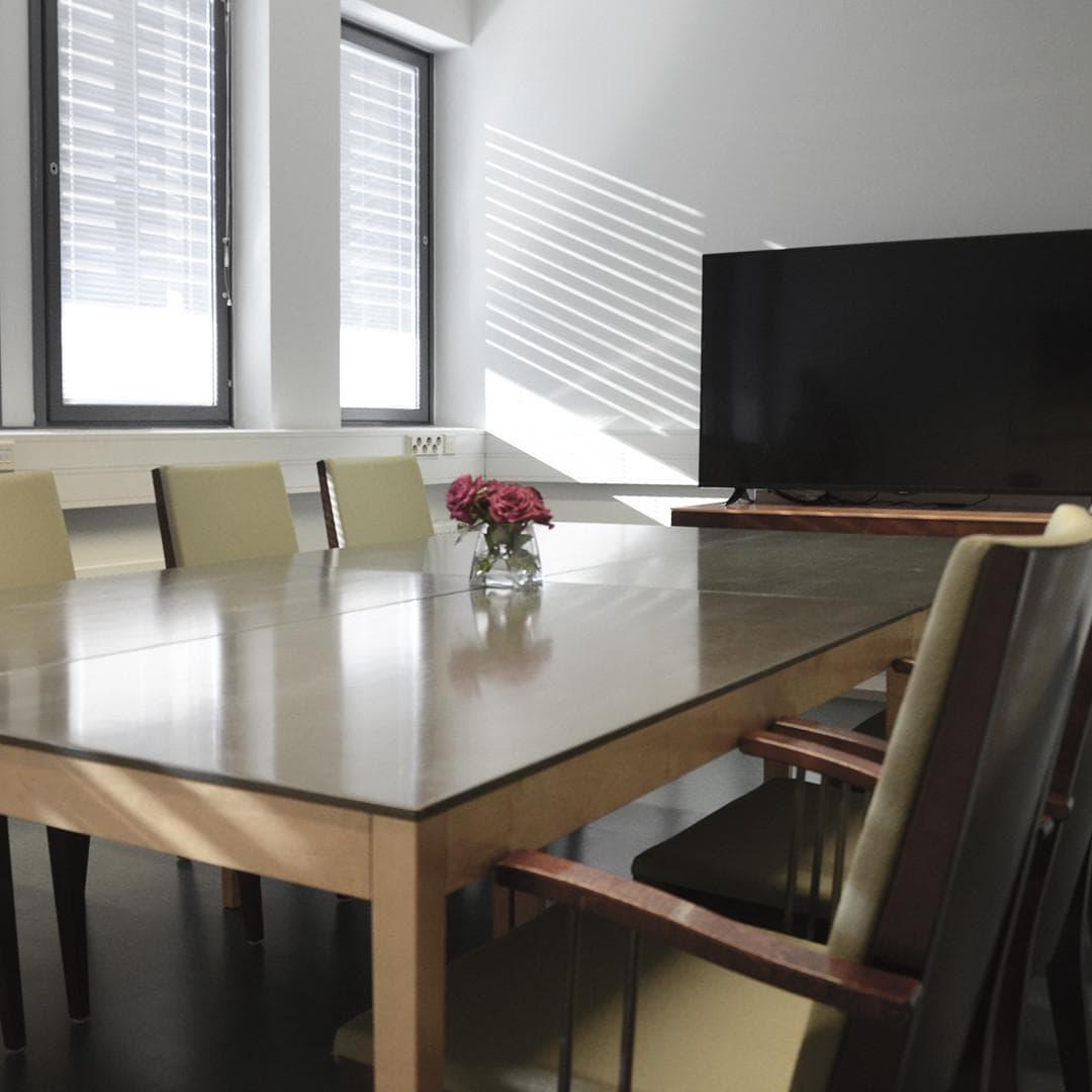 Pieneen kokouskabinettiin paistaa syksyinen aamuaurinko, pöydällä on ruusuja.