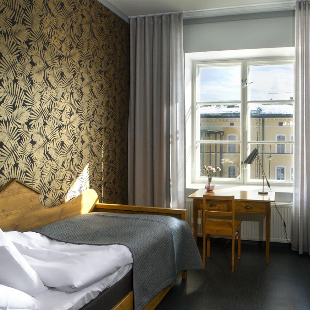 Jaakko Heikkilän suunnittelemassa huoneessa on puusänky ja kirjoituspöytä vanhan ajan malliin.